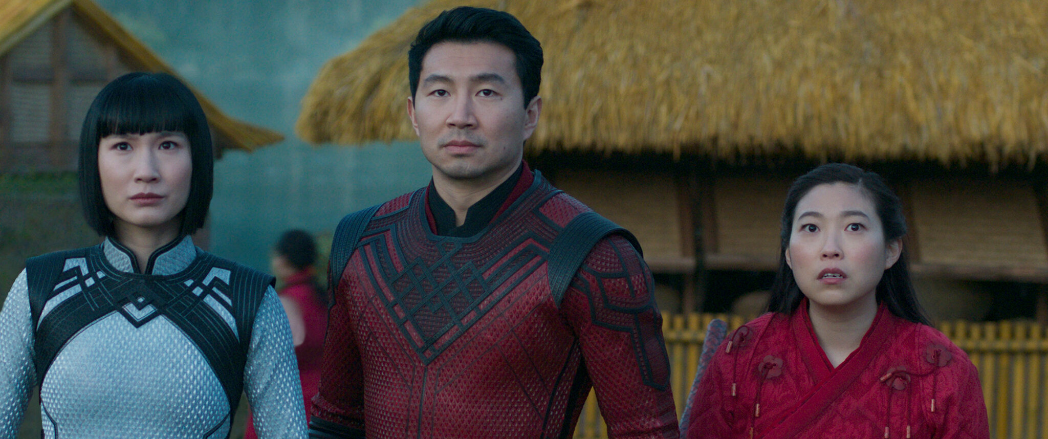 Cena do filme Shang-Chi e a Lenda dos Dez Anéis. A cena mostra 3 pessoas asiáticas em pé, usando roupas de guerra e olhando para frente com expressões de medo.