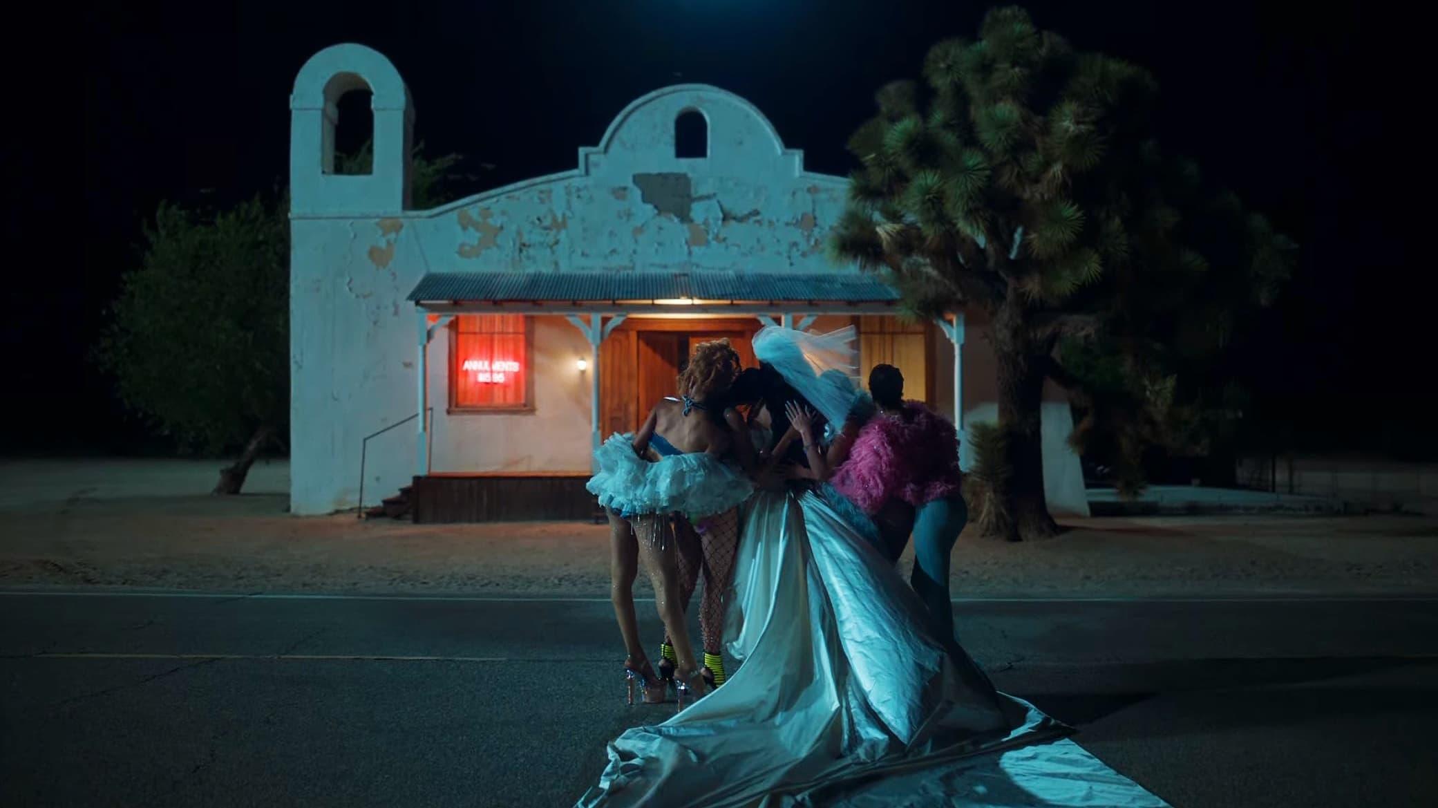 Cena de star-crossed: the film. A imagem mostra um grupo de amigas no meio de uma rua, durante a noite, em frente à uma igreja antiga. O grupo de amigas está de costas para a câmera, que fotografa de frente a igreja. Todas elas usam roupas extravagantes e coloridas, abraçando a personagem de Kacey Musgraves ao centro, vestida de noiva. A igreja é pequena e branca, com a pintura descascando, e tem uma porta no meio e janelas nas laterais, por onde brilha uma luz alaranjada. Na frente da igreja, em uma calçada de pedras, existe uma árvore.