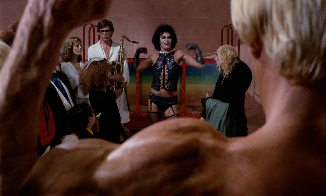 Cena do filme The Rocky Horror Picture Show. Na imagem, em um primeiro plano, vemos o braço flexionado e musculoso do personagem Rocky, um homem branco e loiro, que está de costas e só aparece parcialmente. Em um segundo plano, atrás do braço de Rocky, vemos, da esquerda para a direita, Janet e Brad, uma mulher e um homem brancos, ambos aparentando cerca de 30 anos e vestindo roupões brancos; à frente deles, Magenta, uma mulher branca de cabelos encaracolados vestindo um vestido preto e de lado para a câmera; Frank, o personagem principal, vestindo um corset preto e maquiagem e flexionando os braços; e Riff Raff, um homem branco, de cabelos loiros e longos somente na lateral da cabeça, segurando uma toalha e encarando Frank.